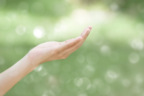 empty human hand with bokeh background in the garden