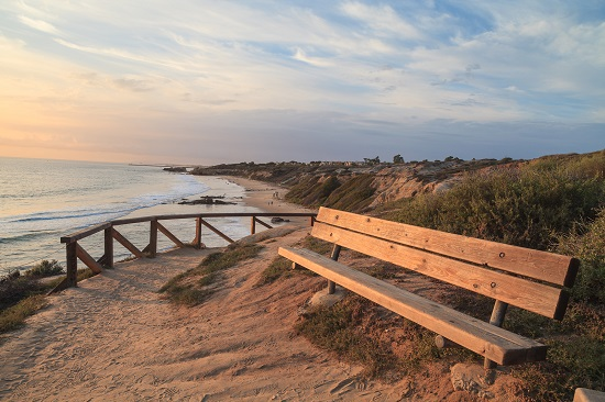 Bench along an outlook with a view of Crystal Cove Beach at sunset, Newport Beach and Laguna Beach line in Southern California